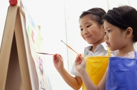 Young girls standing side by side, painting on easel - Asia Images Group