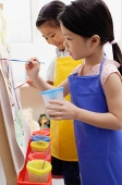 Young girls in blue and yellow aprons painting on easel - Asia Images Group