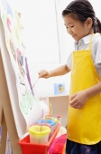 Young girl in yellow apron,  painting on easel - Asia Images Group