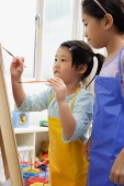 Two girls painting on easel - Asia Images Group