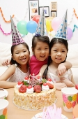 Three girls celebrating a birthday, smiling at camera - Asia Images Group