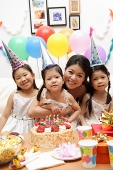 Mother with three girls celebrating a birthday - Asia Images Group