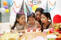Mother with three girls celebrating a birthday, blowing candles on cake - Asia Images Group