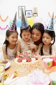 Mother with three daughters celebrating a birthday, looking at cake - Asia Images Group