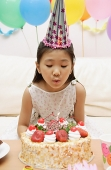 Girl blowing out candle on a cake - Asia Images Group