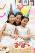 Mother with two girls celebrating a birthday, smiling at camera - Asia Images Group