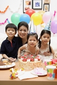 Mother with three children celebrating a birthday - Asia Images Group