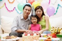 Family with one child sitting with birthday cake, portrait - Asia Images Group