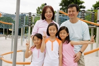 Family at playground, smiling at camera - Asia Images Group