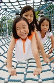 Girls at playground, crawling through net tunnel - Asia Images Group