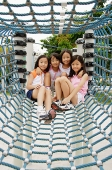 Four girls at playground, sitting in net tunnel - Asia Images Group