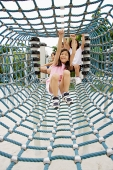 Girls going through net tunnel in playground - Asia Images Group