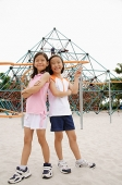Girls at playground, standing back to back, smiling at camera - Asia Images Group