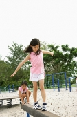 Girls walking on balance beams - Asia Images Group