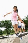 Three girls walking on balance beams - Asia Images Group