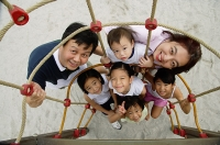 Family at playground, smiling at camera, high angle view - Asia Images Group