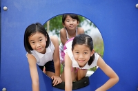 Girls in playground, climbing through a hole - Asia Images Group