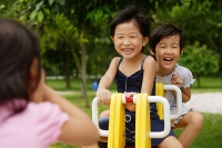 Young girls in playground, playing on seesaw - Asia Images Group