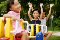Three girls on a seesaw, arms outstretched - Asia Images Group