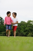 Two girls on grass, walking, side by side - Asia Images Group