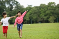 Two girls running on grass, side by side, arms outstretched - Asia Images Group