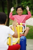 Two girls on a seesaw, raising their hands - Asia Images Group