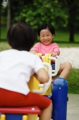 Two girls playing on a seesaw - Asia Images Group