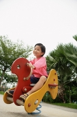 Young girl in playground, riding hobby horse - Asia Images Group
