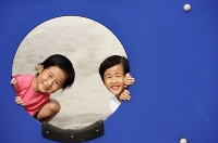 Two girls in playground, looking through hole - Asia Images Group
