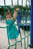 Young boy in playground, holding on to net - Asia Images Group