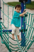 Young boy in playground, walking on net bridge - Asia Images Group