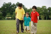 Boys walking on grass, side by side - Asia Images Group