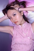 Woman in cheongsam top, hands on head - Asia Images Group