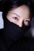 Young woman with turtleneck pulled up over half of face - Asia Images Group