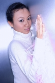 Young woman in white turtleneck leaning on wall - Asia Images Group