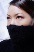 Young woman with turtleneck pulled up over half of face, looking away - Asia Images Group