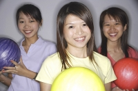 Women holding bowling balls, smiling at camera - Asia Images Group