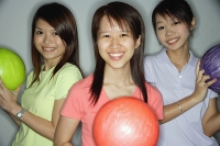 Three young women holding bowling balls, smiling at camera - Asia Images Group