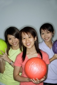 Three young women with bowling balls, smiling - Asia Images Group