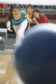Woman bowling, friends behind her watching - Asia Images Group