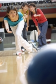Woman bowling, friends watching - Asia Images Group