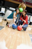 Three women crouching in bowling alley, holding bowling balls - Asia Images Group