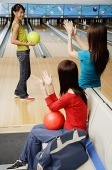 Women in bowling alley, cheering friend on - Asia Images Group