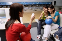 Women in bowling alley, posing for friends phone camera - Asia Images Group