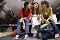 Women sitting side by side in bowling alley - Asia Images Group