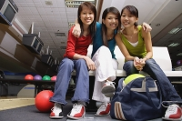 Women sitting side by side in bowling alley, smiling at camera - Asia Images Group