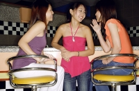 Women at bar counter, talking to each other - Asia Images Group