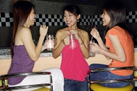 Women at bar counter, with drinks, talking to each other - Asia Images Group