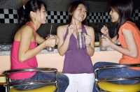 Women at bar counter, having drinks - Asia Images Group
