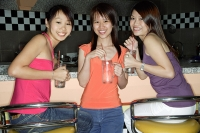 Women at bar counter, holding drinks, smiling at camera - Asia Images Group
